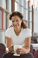 Hispanic businesswoman holding coffee cup
