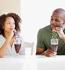 African father and daughter drinking with straws