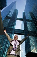 low angle portrait of mature businessman in front of office building celebrating