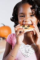 African girl eating Halloween cookie
