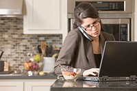 Hispanic businesswoman using laptop and telephone
