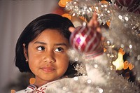 Hispanic girl putting ornament on Christmas tree