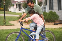 Hispanic father helping daughter ride bicycle