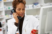 African female pharmacist talking on telephone