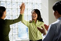 Businesswomen high_fiving next to water cooler