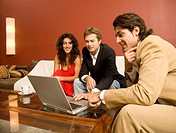 Man in suit showing laptop to couple