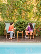 Two women with drinks in patio chairs next to pool