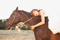 Hispanic woman hugging horse´s neck in sunlight