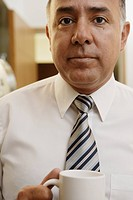 Close up of middle_aged businessman with coffee mug