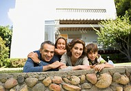 Portrait of family leaning on stone wall