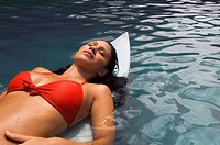 Pacific Islander woman laying on surfboard in water