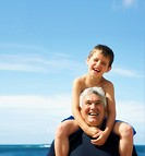 Grandson on grandfather´s shoulders at beach