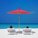 Couple in beach chairs under umbrella