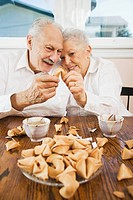 Senior couple eating fortune cookies