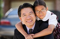 Asian father and daughter hugging outdoors
