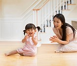 Asian mother and baby daughter clapping