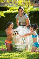 Hispanic mother and daughters washing dog