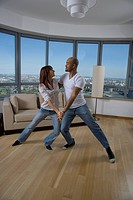Multi_ethnic couple dancing in livingroom