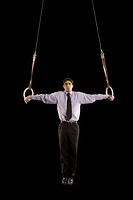 Hispanic businessman performing on gymnastics rings