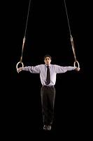 Hispanic businessman performing on gymnastics rings