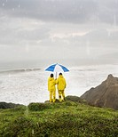 Hispanic couple under umbrella on cliff