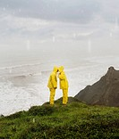 Hispanic couple in rain gear kissing on cliff