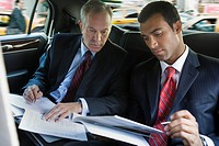 Businessmen reviewing paperwork in limousine