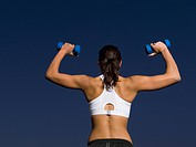 Rear view of mixed race woman doing shoulder presses with dumbbells