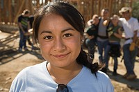 Close up of smiling Hispanic woman at construction site