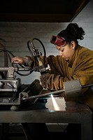 Hispanic female welder working with torch