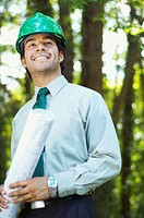 Hispanic architect holding blueprint and wearing green hard hat