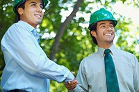 Hispanic businessmen in green hard hats shaking hands outdoors