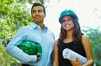 Hispanic business people with green hard hats