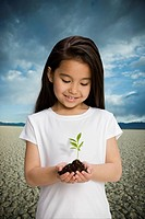 Chinese girl holding seedling in desert