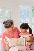 Hispanic grandmother and granddaughter looking at scrapbook