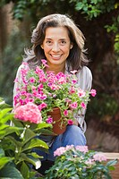 Hispanic woman holding flowers in garden