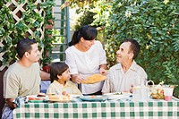 Multi_generational Hispanic family eating on patio