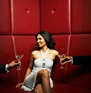 Men offering glamorous mixed race woman cocktails