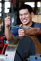 Asian man working with metal in warehouse