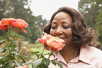 Middle_aged African woman smelling roses outdoors