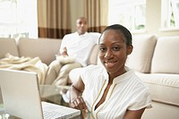 African woman with laptop in livingroom