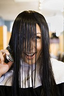 Pacific Islander woman talking on cell phone in salon