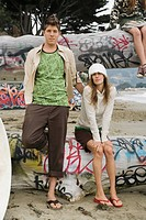 Multi_ethnic couple sitting on graffiti logs