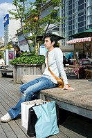 Young man sitting on the staircase by the shopping bags