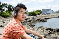 Young man with headphone by the river