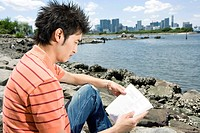 Young man reading the book by the river
