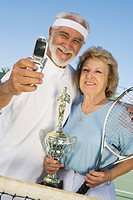 Tennis players holding award cup and photographing