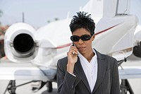 Mid_adult African_American businesswoman standing in front of private plane and talking on phone.
