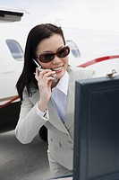 Mid_adult businesswoman using mobile phone outside of airplane.
