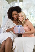 Young woman with friend holding gift at bridal shower